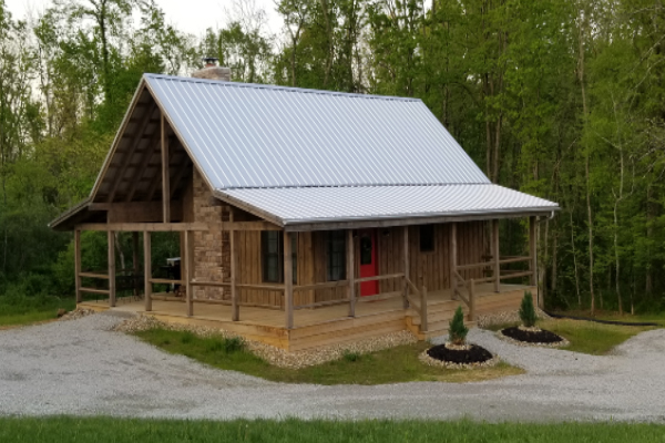 log cabin with wrap around porch and metal roof